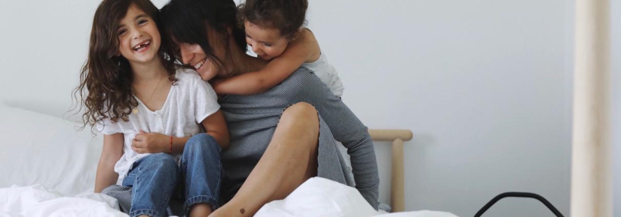maman avec fillettes assises sur le lit