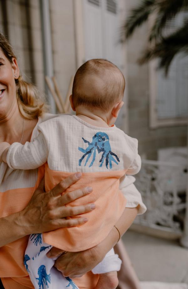 Bebe de dos dans les bras de maman